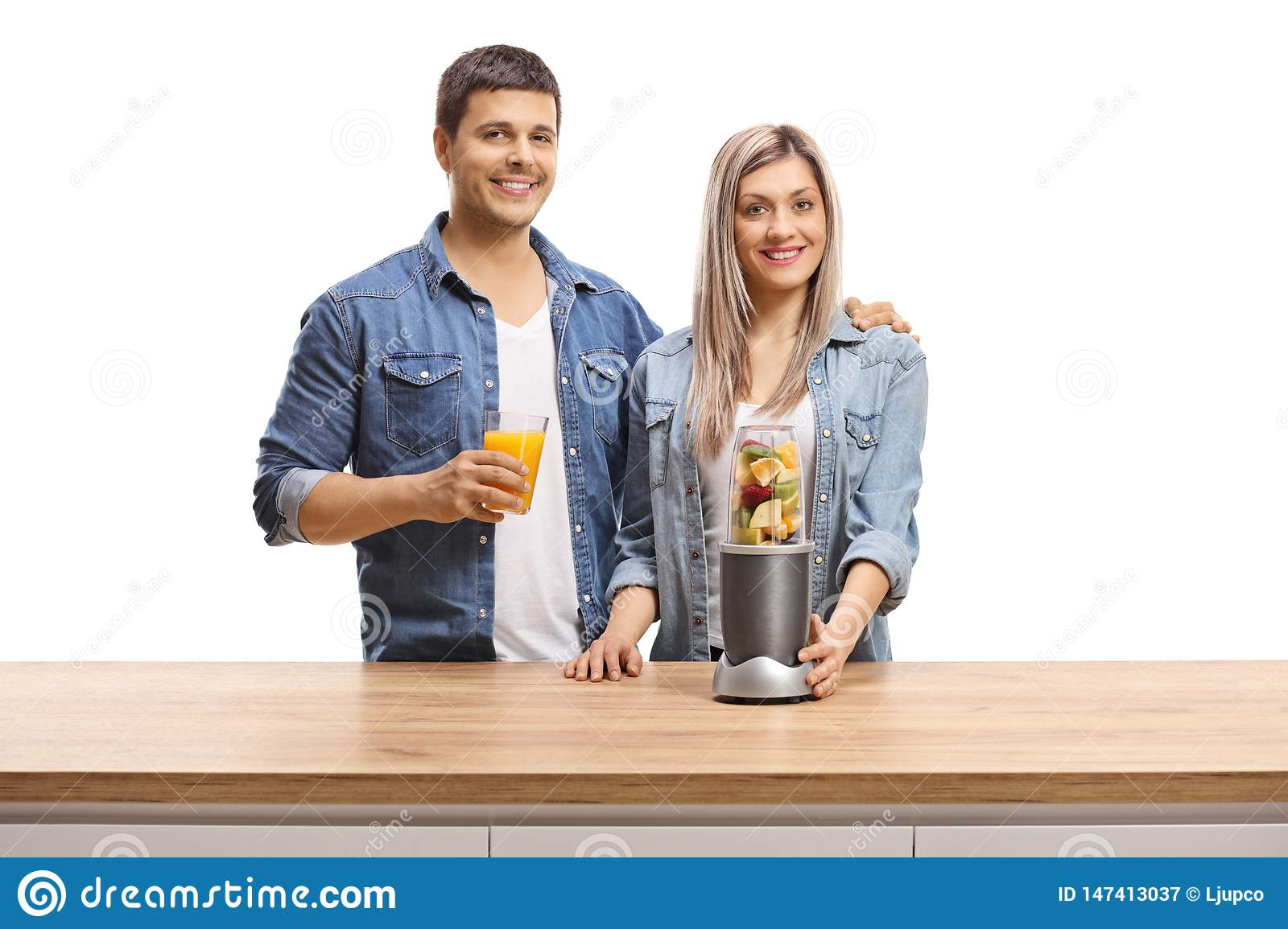 Young man and woman with fruits in a blender and a glass of juice smiling at the camera