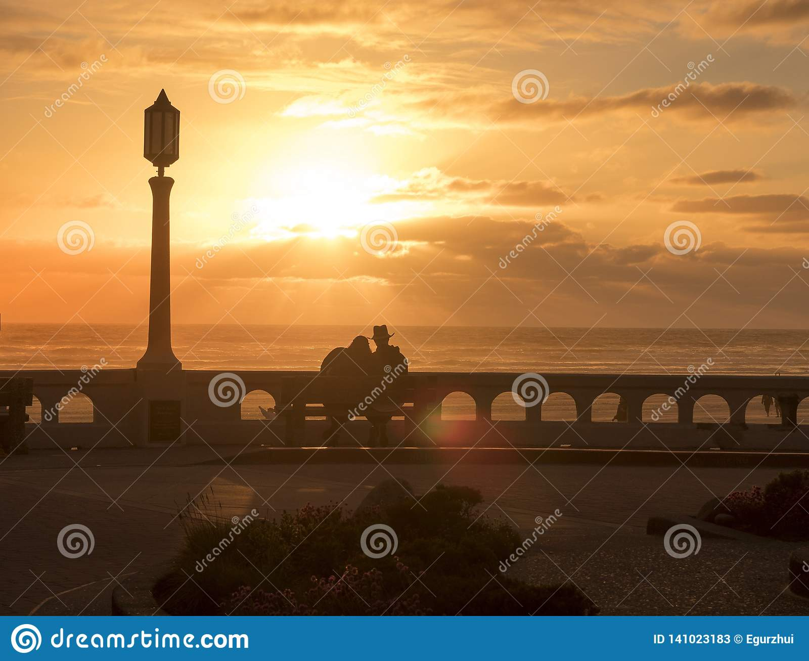 A young man and a woman in love sitting on a bench on the seashore and enjoying a beautiful sunset.