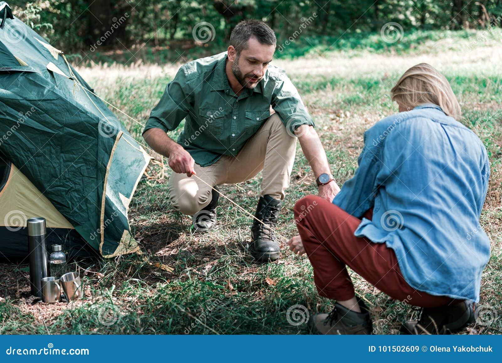 Men com pitching the tent