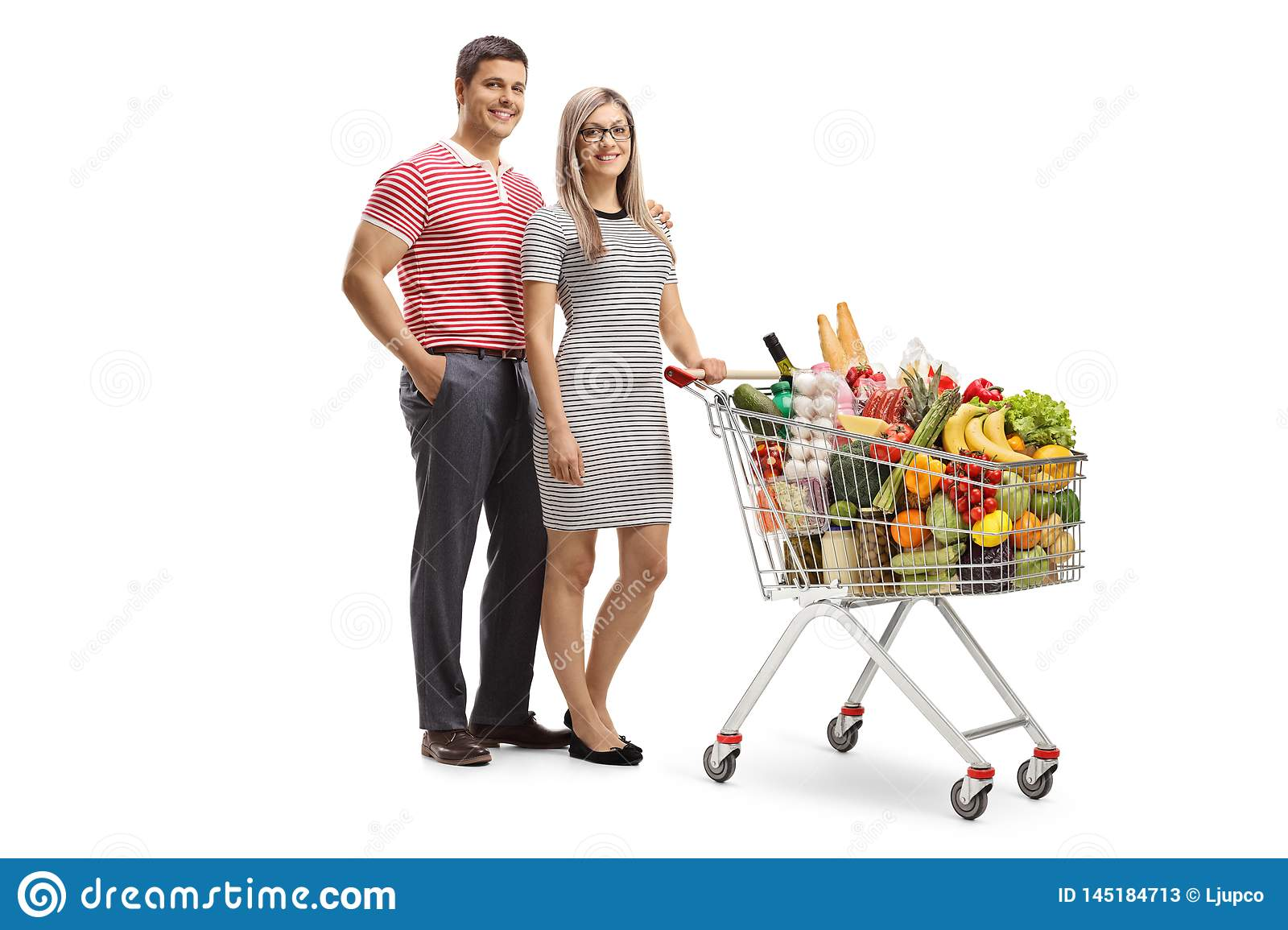 Young man and woman posing with a full shopping cart