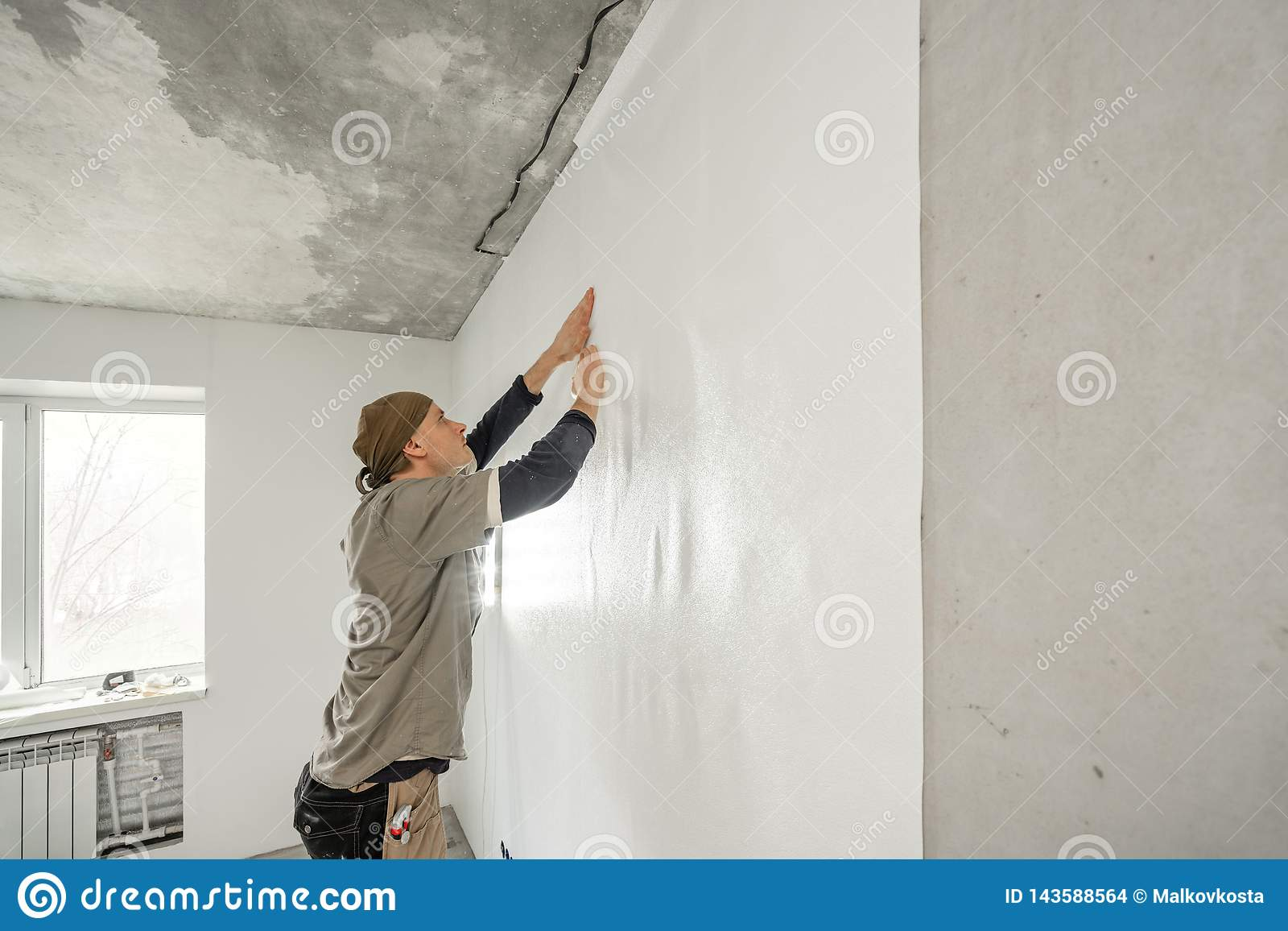 Young man, worker glueing wallpapers on concrete wall. Repair the apartment. Home renovation concept. White Wallpaper
