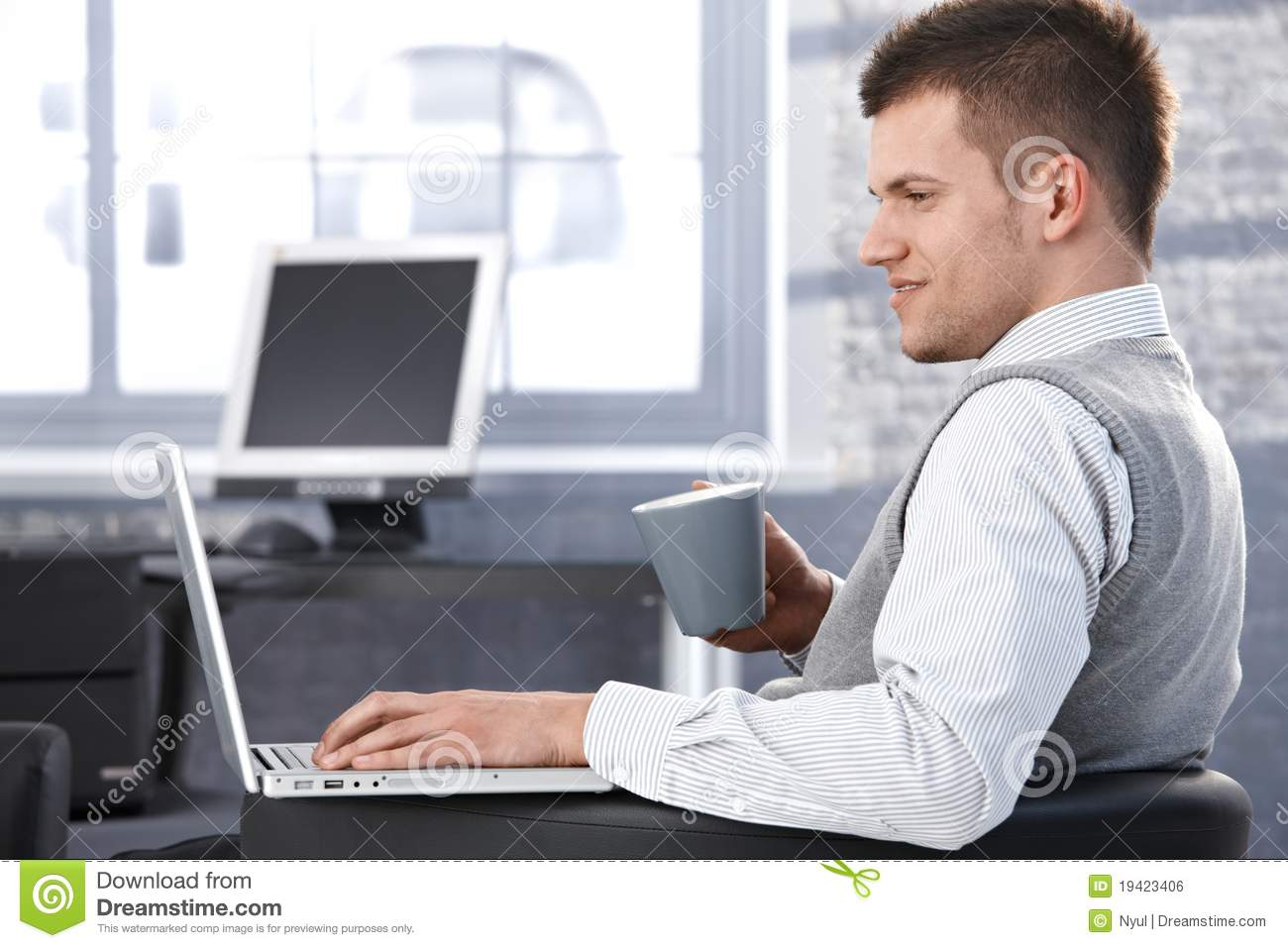 Young Man Working In Office Using Laptop Royalty Free