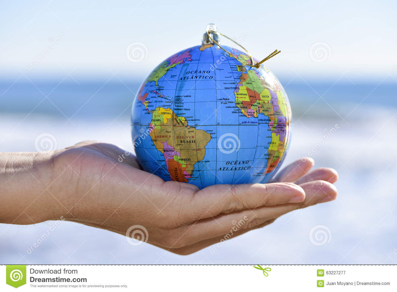 young man with a world globe as a christmas ball in his hand stock