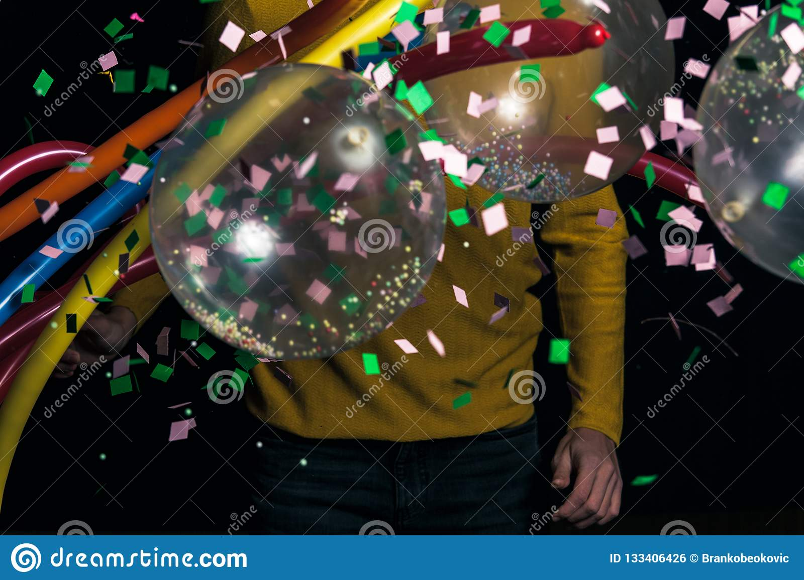 Young man in yellow sweater with balloons partying
