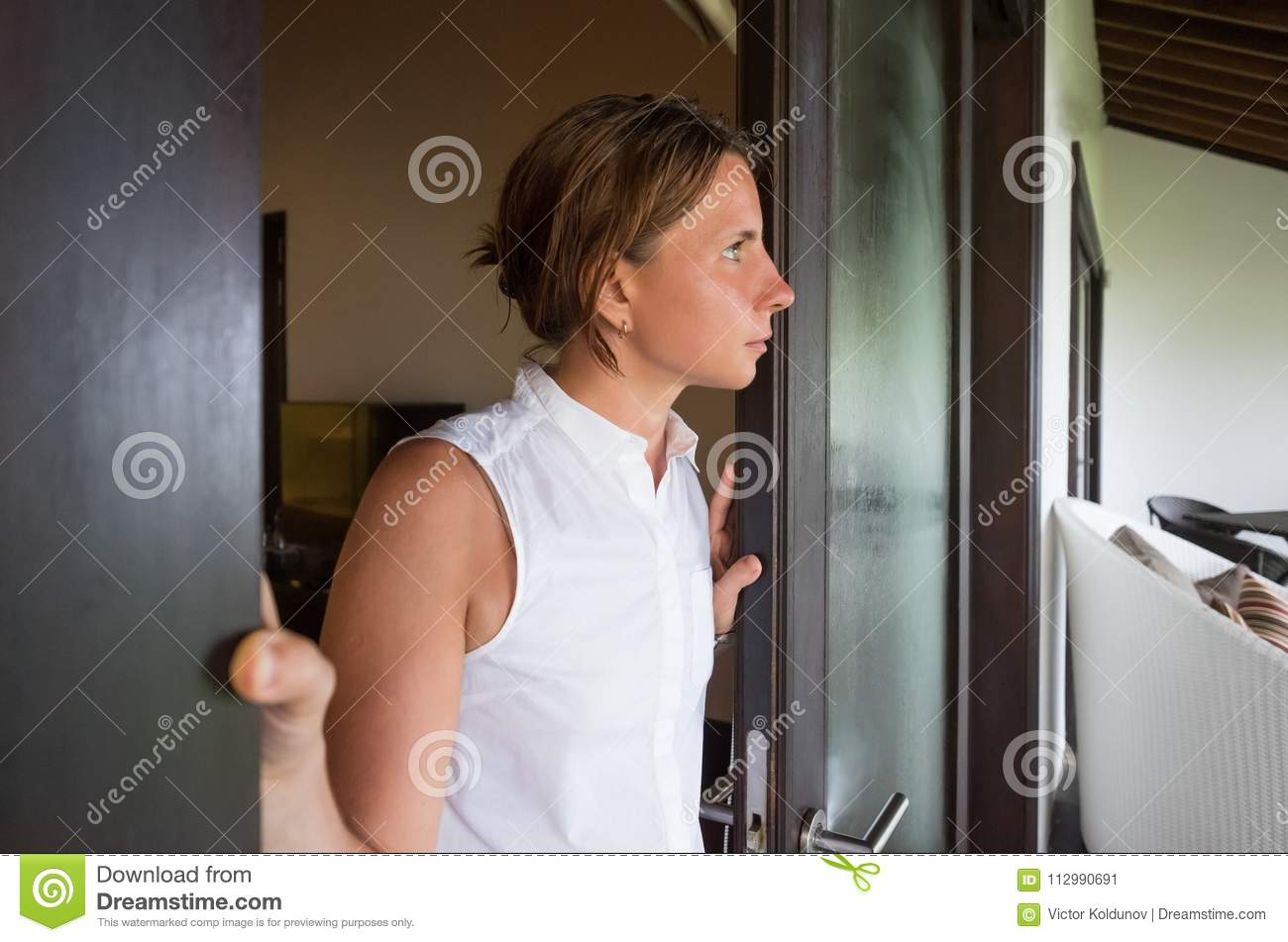 Young mature woman opening the window in the morning to breathe fresh air. She is alone and sad.