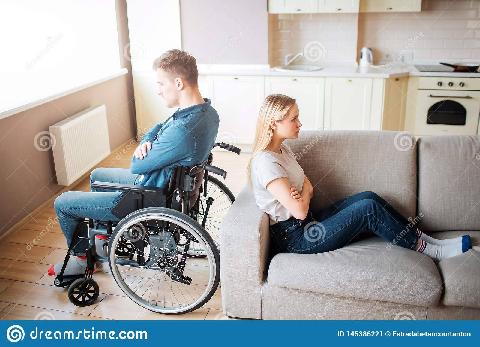 Young man with special needs and healthy woman sit back to back in room. Argue and quirrel. Worker with disability and