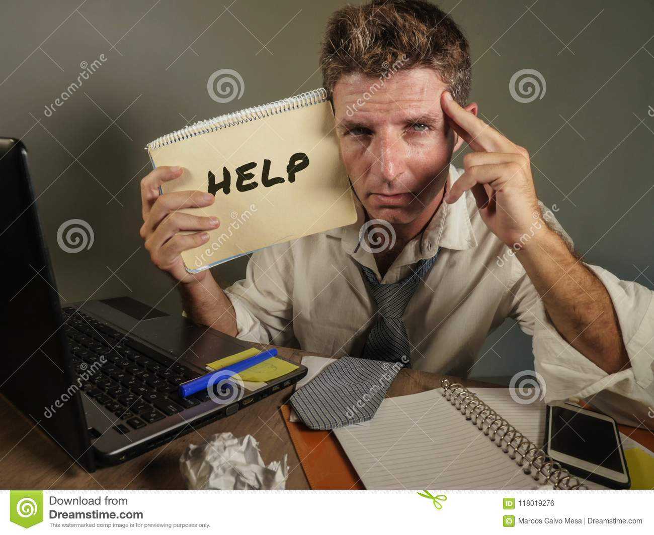 Young messy and depressed business man showing notepad asking for help desperate and sad at office laptop computer desk looking ov