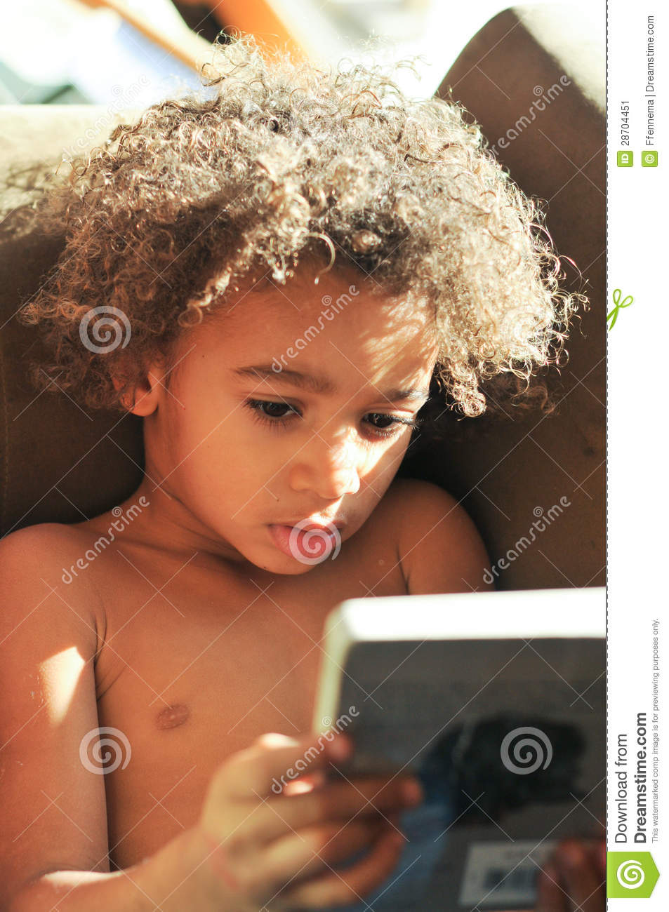 Young Mixed Race Boy With Curly Hair Reading Stock Image
