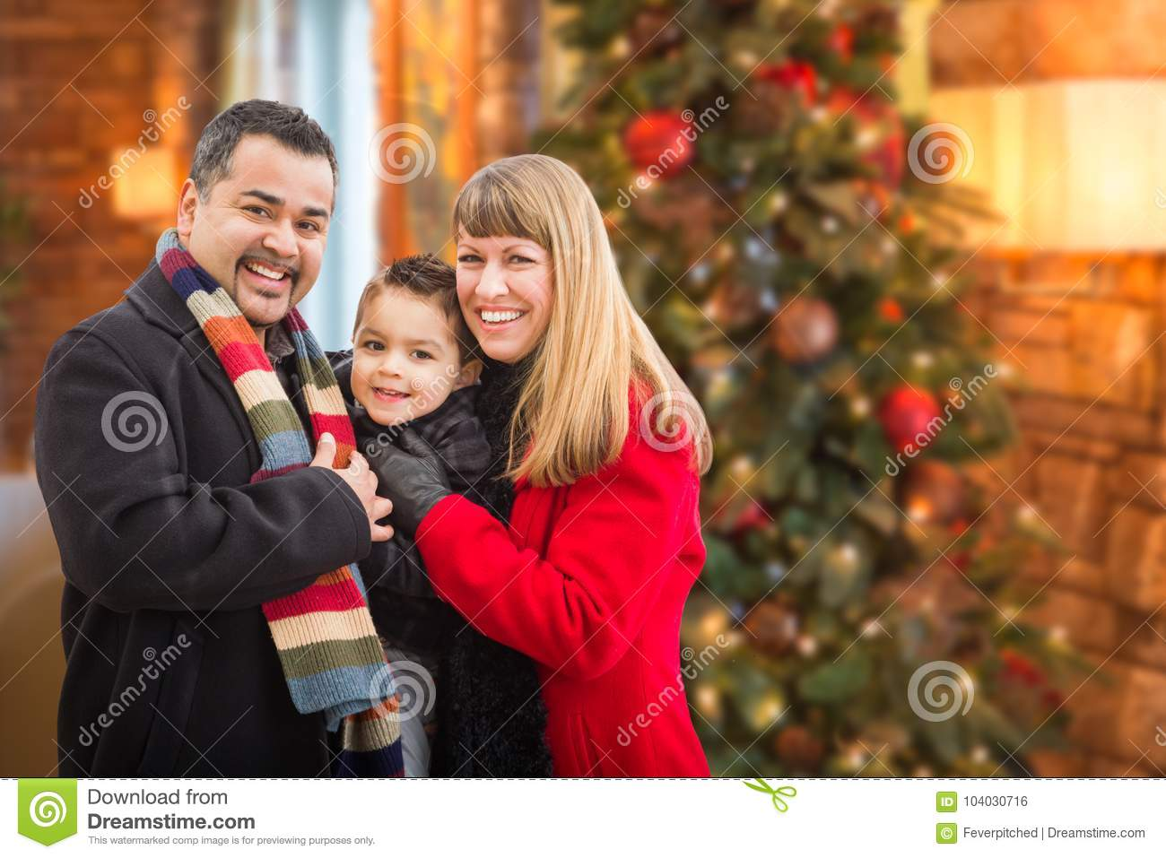 Young Mixed Race Family Portrait In Front of Christmas Tree Indoors.
