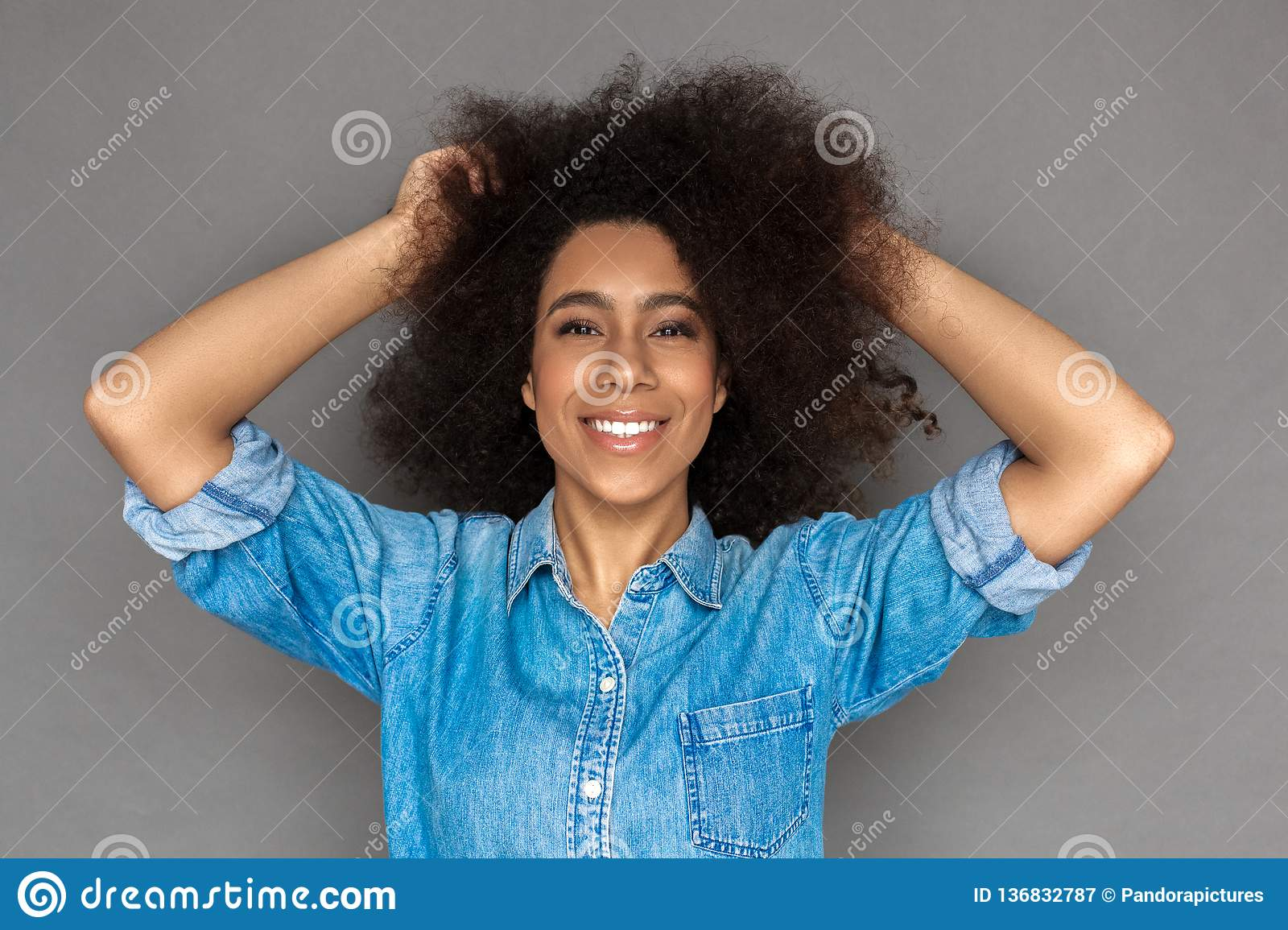 Freestyle. Mulatto woman standing on grey touching hair laughing cheerful close-up