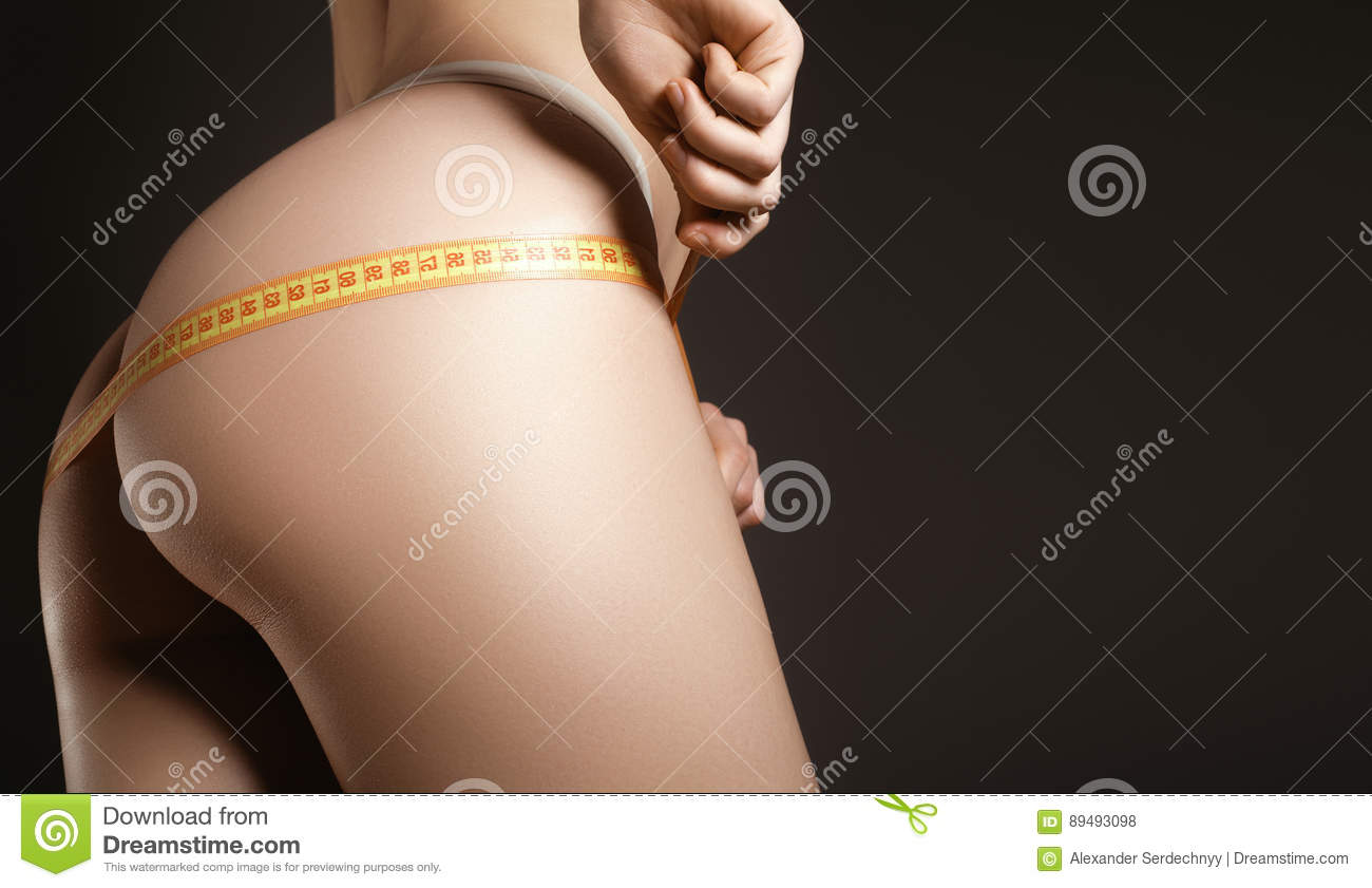 Young model with sports figure measuring her hips. Slim model me