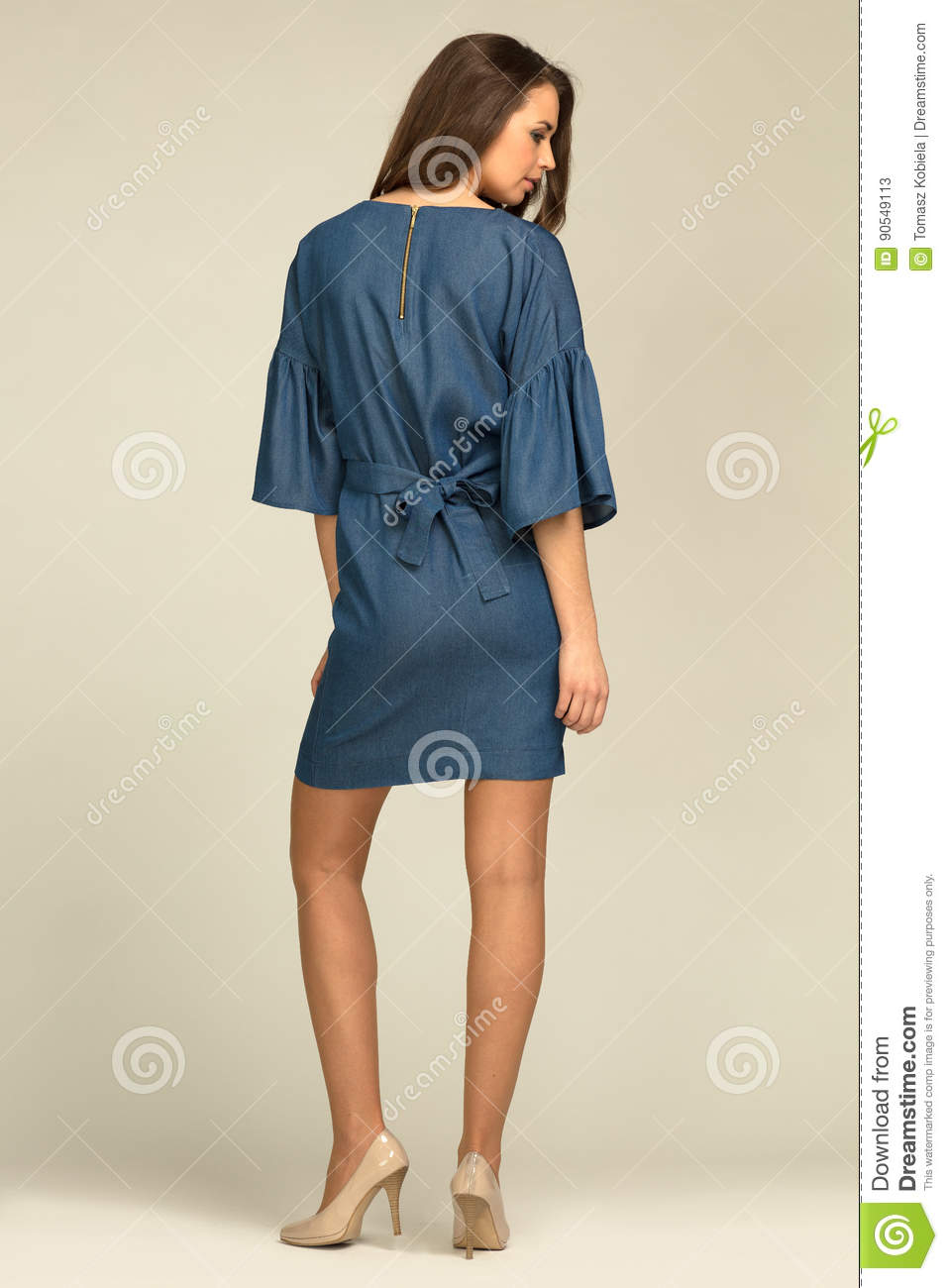 Young model wearing blue, jeans dress with slim body.