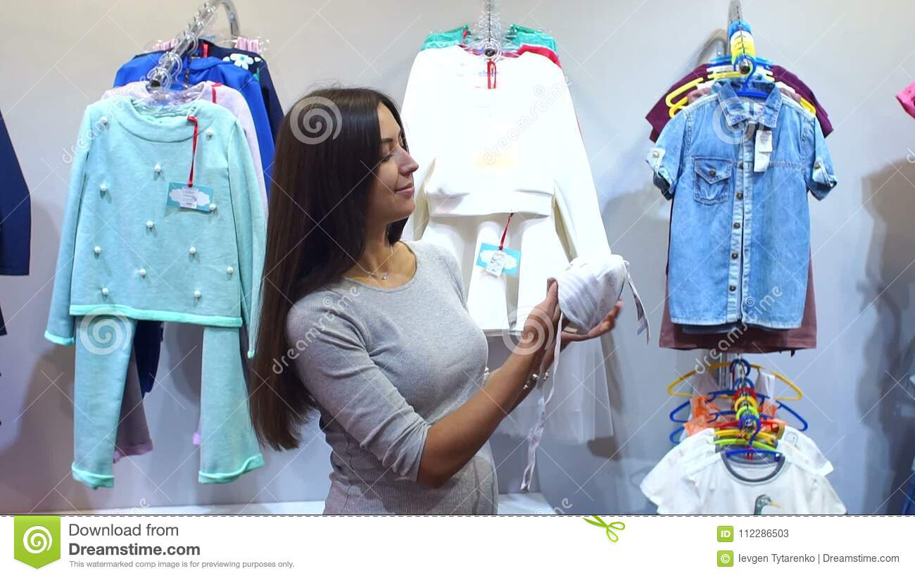 0567ffdb1766c Pregnant Woman Choosing Baby Clothing In Baby Shop Stock Video ...
