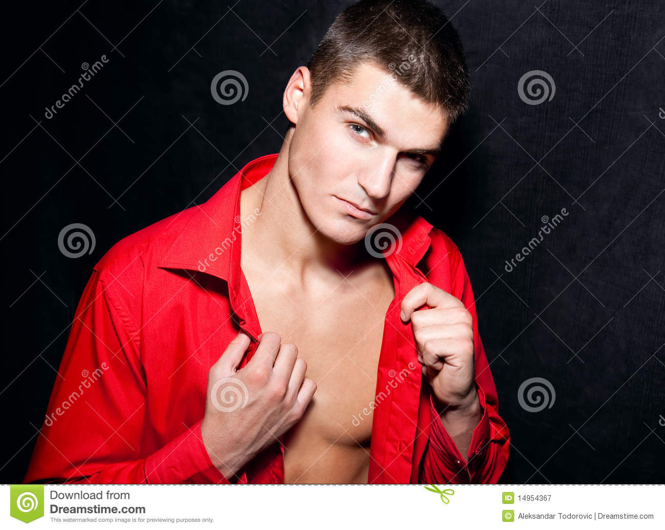 Young modern macho man in red shirt is posing