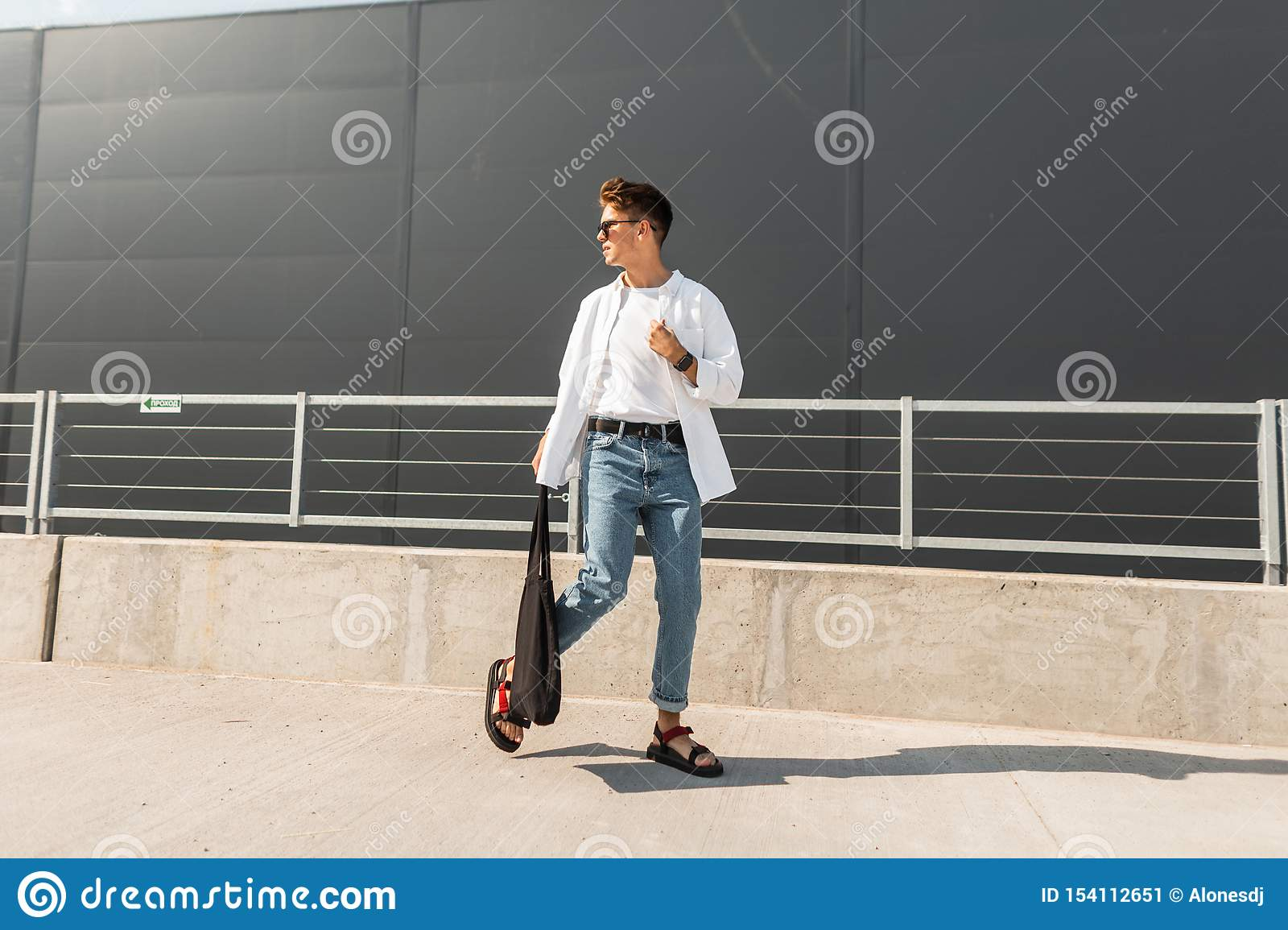 Young modern man model in a white vintage shirt in blue stylish jeans in sunglasses with a black bag walks on the street
