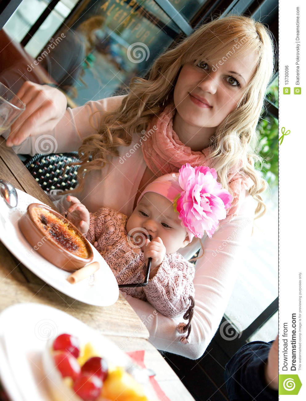 Young mother and baby daughter having breakfast