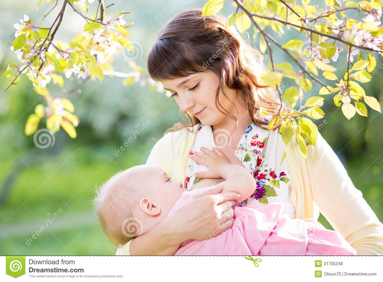 Young mother breastfeeding baby girl sunny day