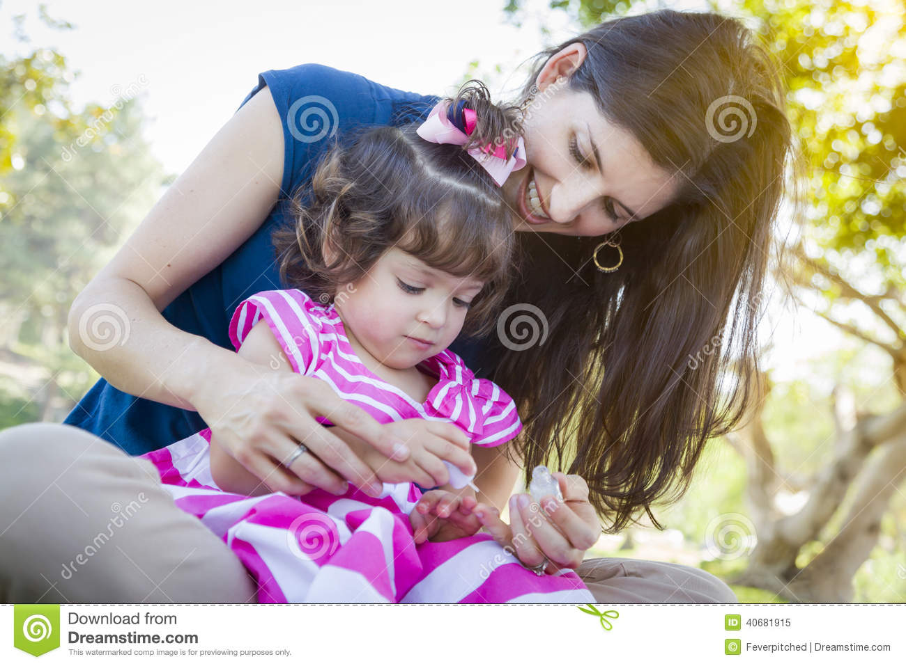 young mother and cute baby girl applying fingernail polish stock