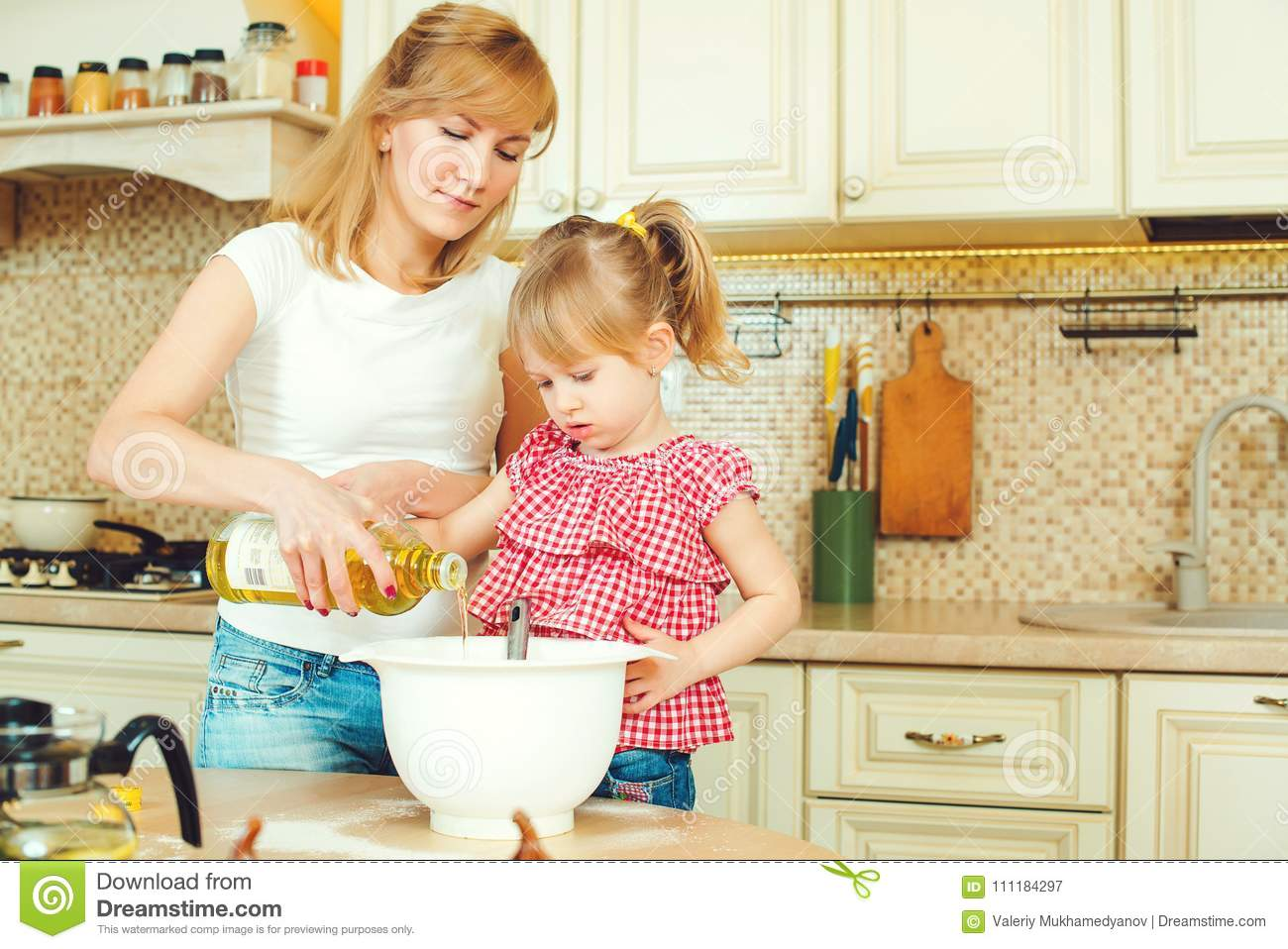 Young mother and cute little daughter preparing the dough, bake cookies and having fun in the kitchen.