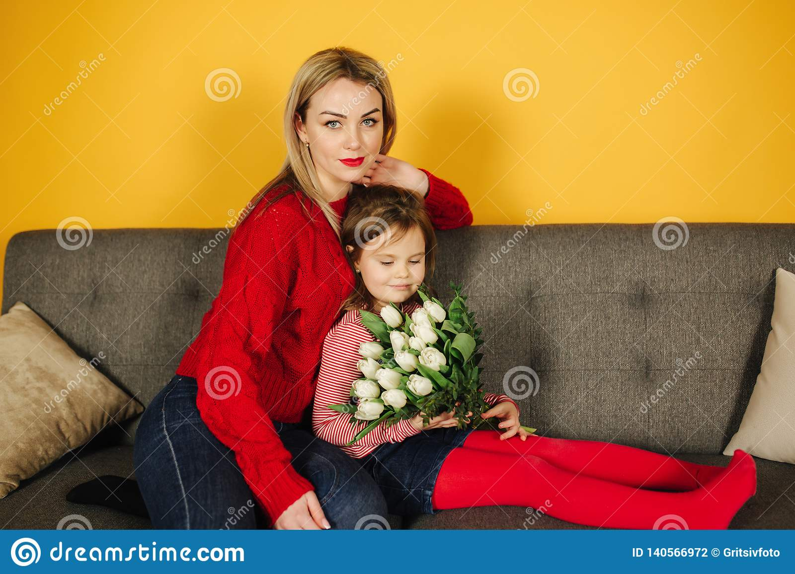 Young mother with doughter sitting on grey sofa. Yellow Background in studio. Flowers 8th of march