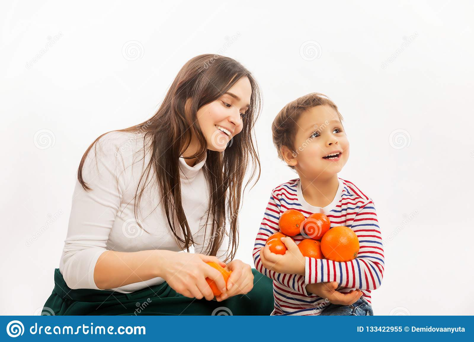 Young mother eats fruit and vegetables with her young son
