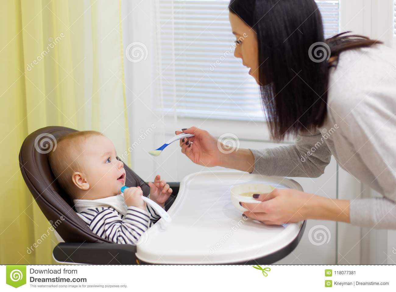 Young mother feeding her little baby son with porridgewho sitting in high baby chair  sc 1 st  Dreamstime.com & Young Mother Feeding Her Little Baby Son With Porridgewho Sitting ...
