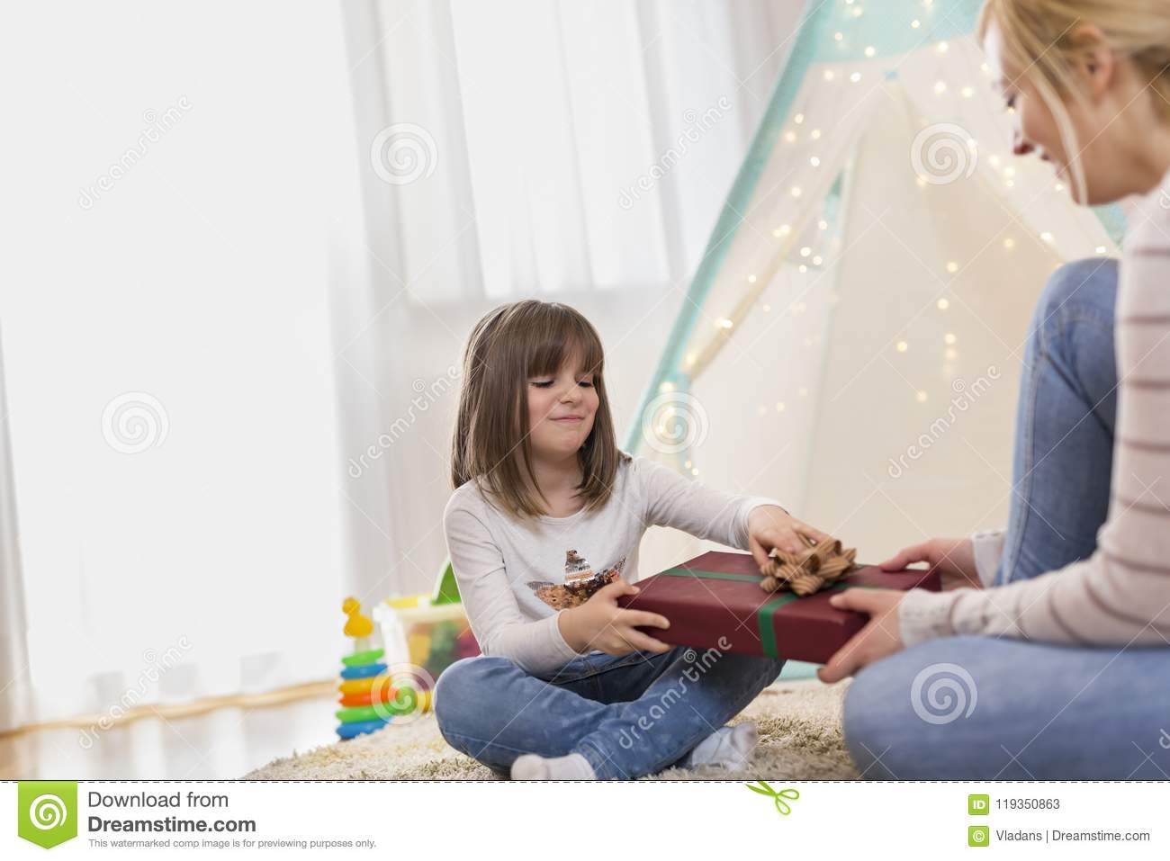 Young Mother Giving A Birthday Present To Her Daughter Focus On The