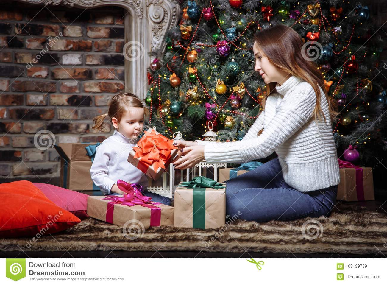Young Mother Giving Her Little Daughter A Christmas Gifts. Stock ...