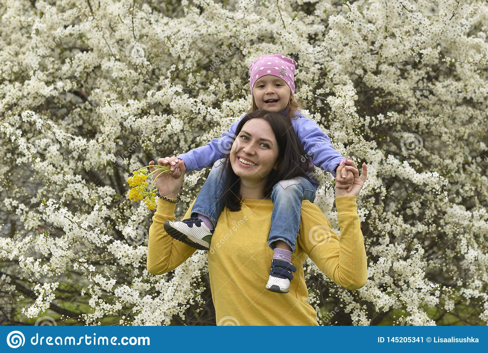 A young mother has put her little daughter on her shoulders and plays with her in the blooming garden