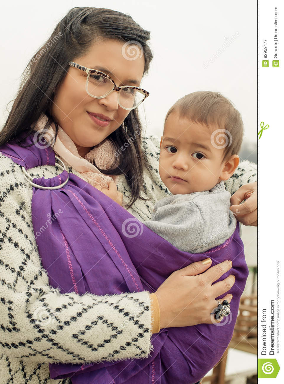 114ce8ecf85 Portrait of a mother carrying her little baby in a baby carrier scarf in  the park