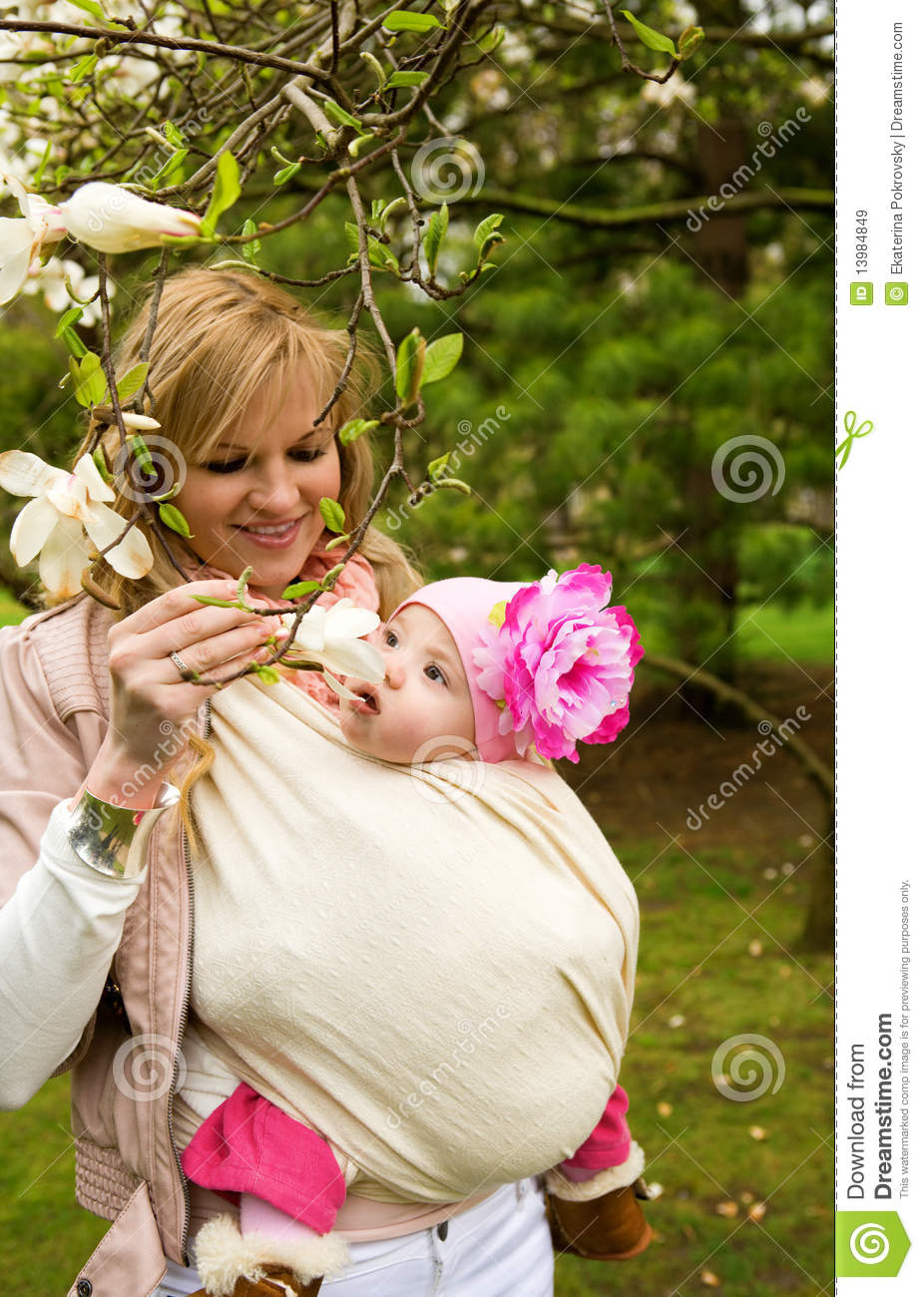 Young mother with her baby daughter in garden
