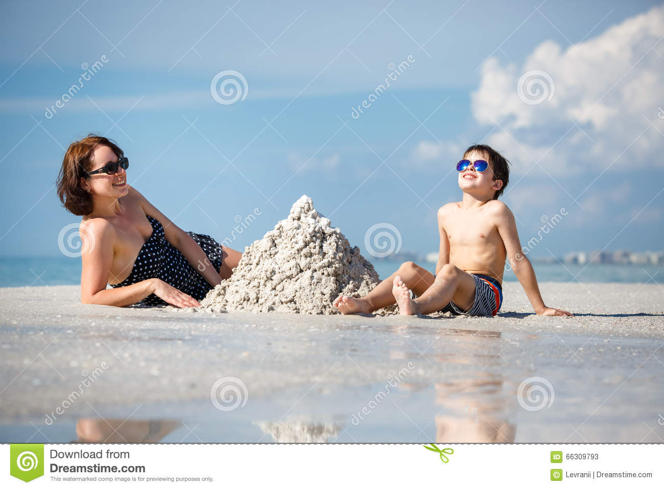 Young mother and her little son building sand castle at beach on Florida  summer holiday vacation