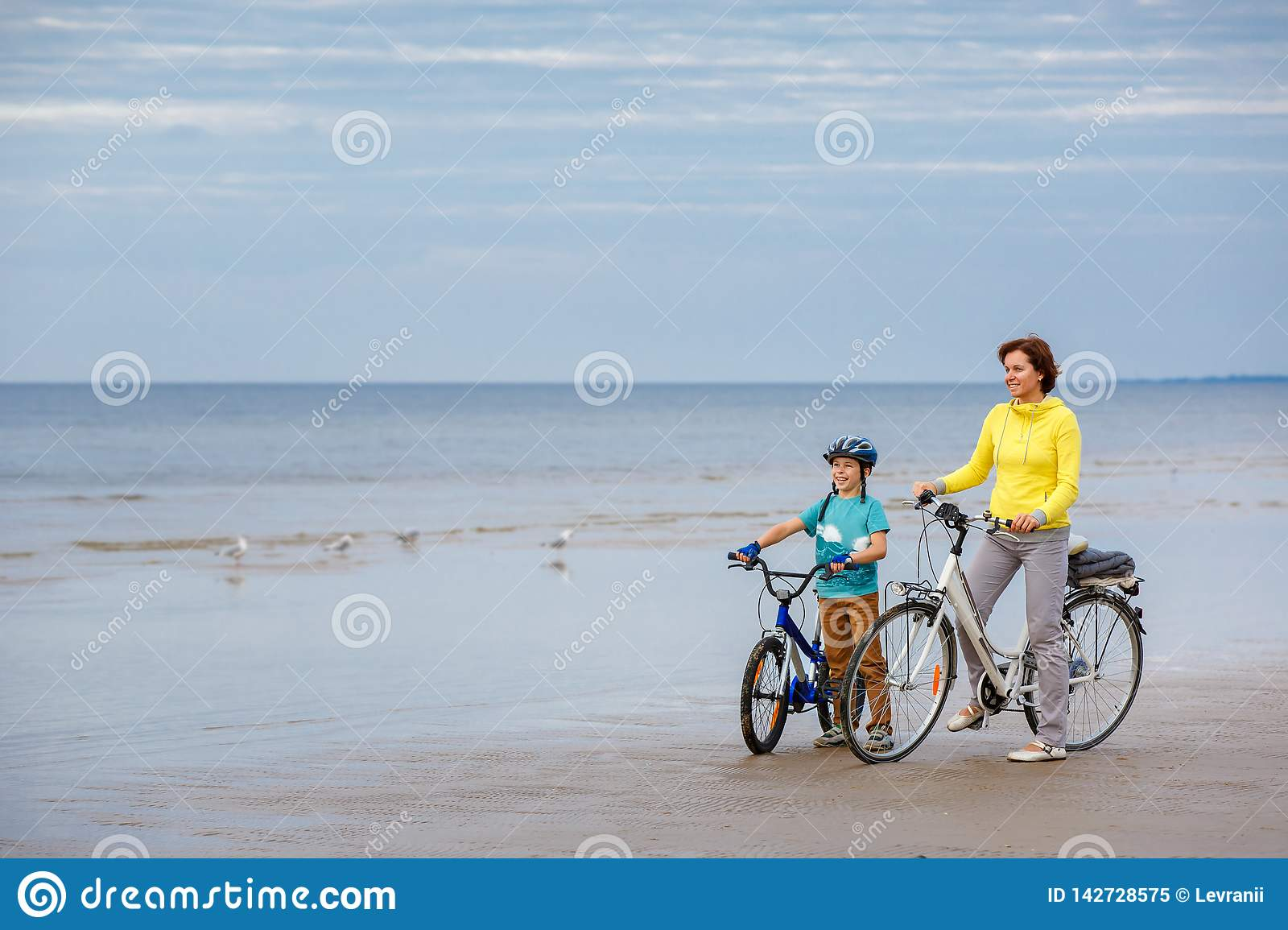 Young mother with her little son riding bicycles on beach. Young mother with her little son on sand beach royalty free stock photo
