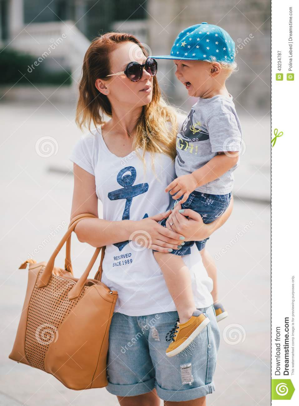Young Mother And Her Son Walking In City Stock Photo