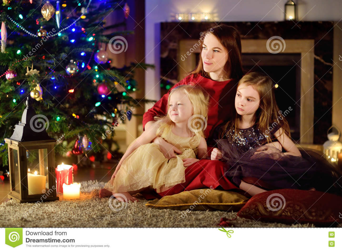 Young Mother And Her Two Daughters Unwrapping Christmas Gifts By A ...