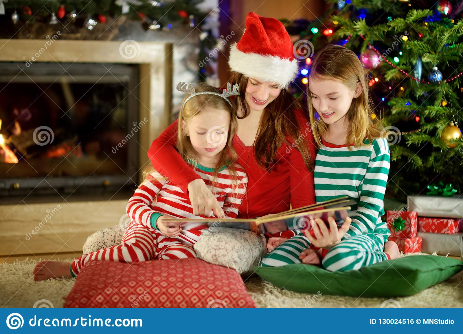 Young Living Christmas Tree.Young Mother And Her Little Daughters Reading A Book By A