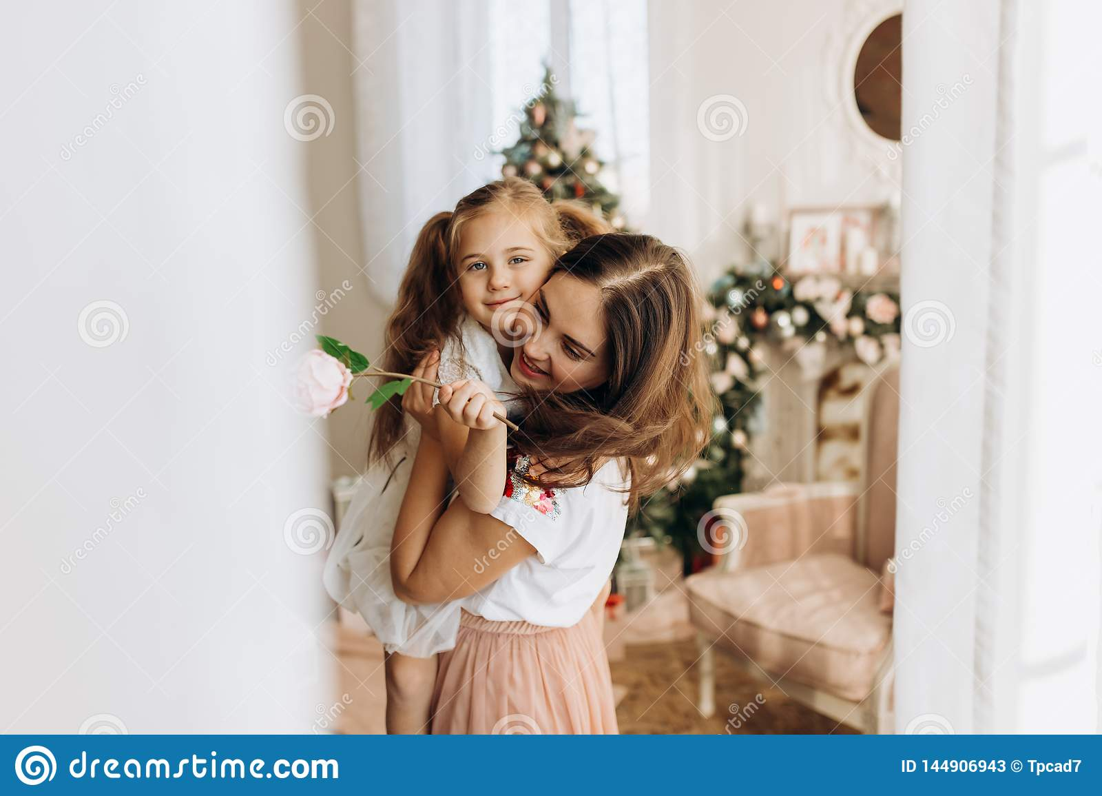Young mother holds on her hands her little daughter in the cozy room with the New Year`s tree