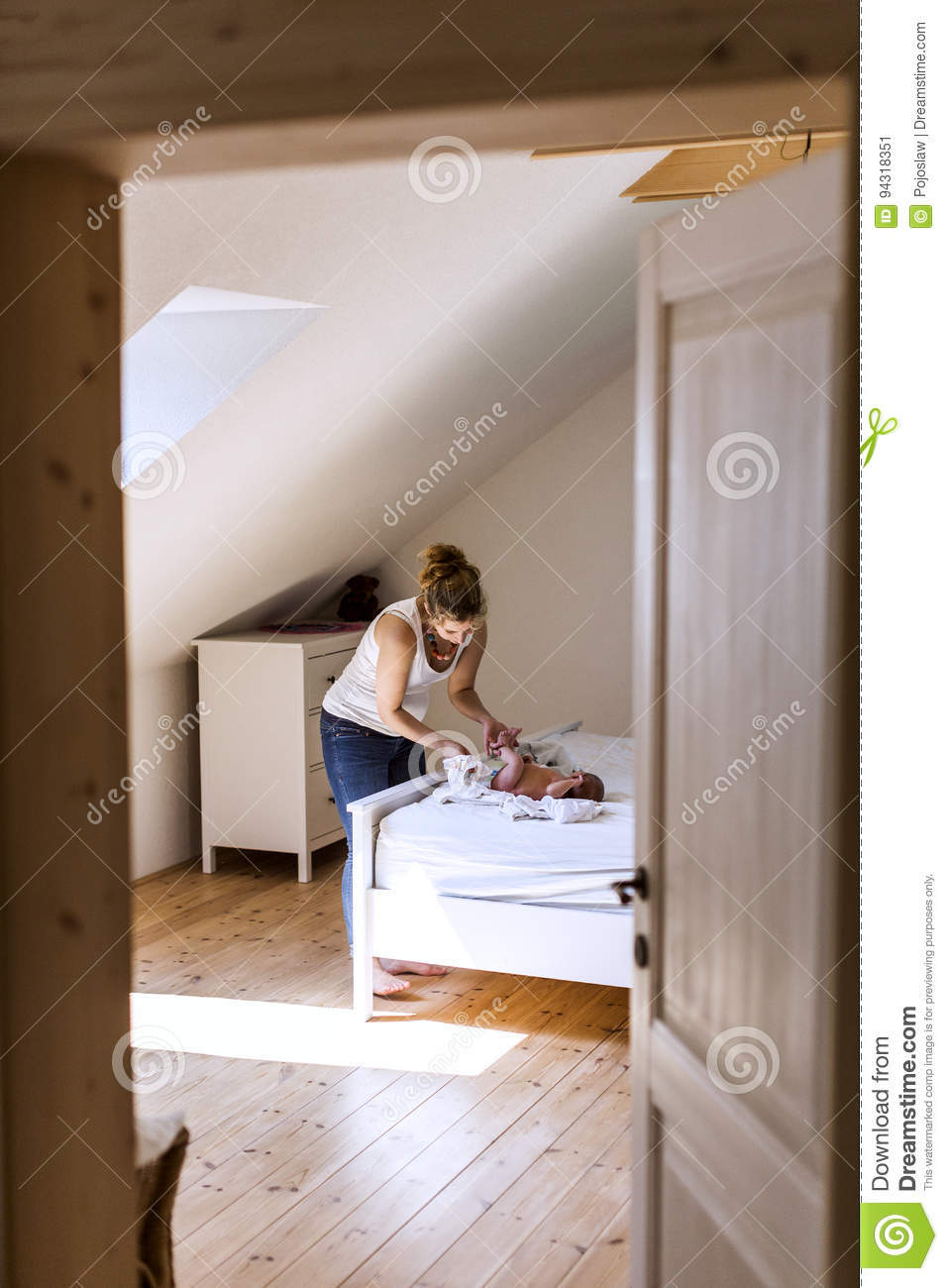 Young mother at home changing diaper to her baby girl.