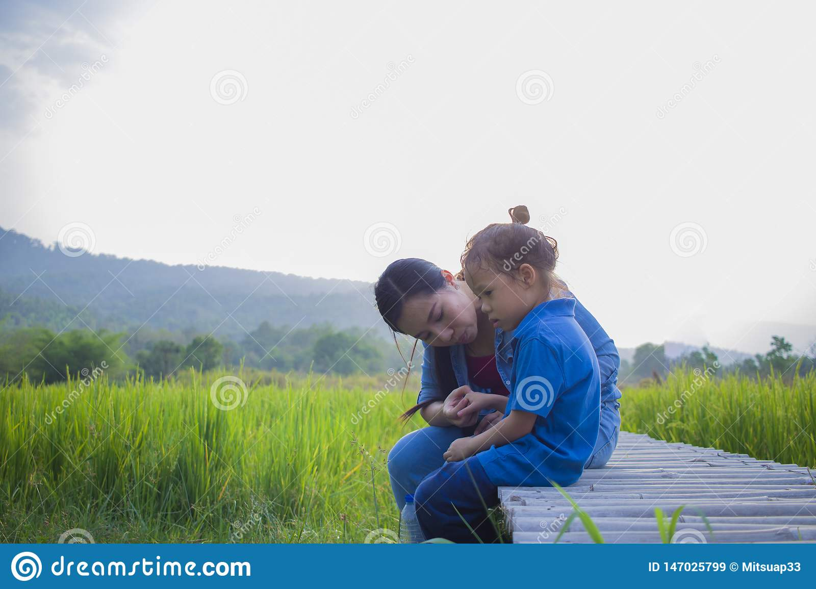 Young mother hugging and soothing a crying little long hair  boy, Asian mother trying to comfort and calm down her crying child