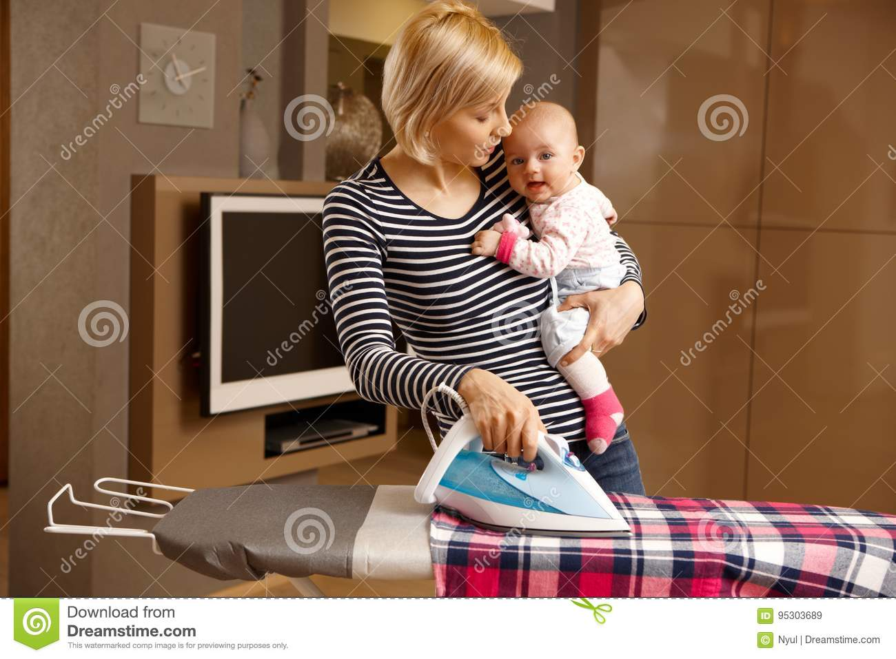 Young mother ironing with baby in arm