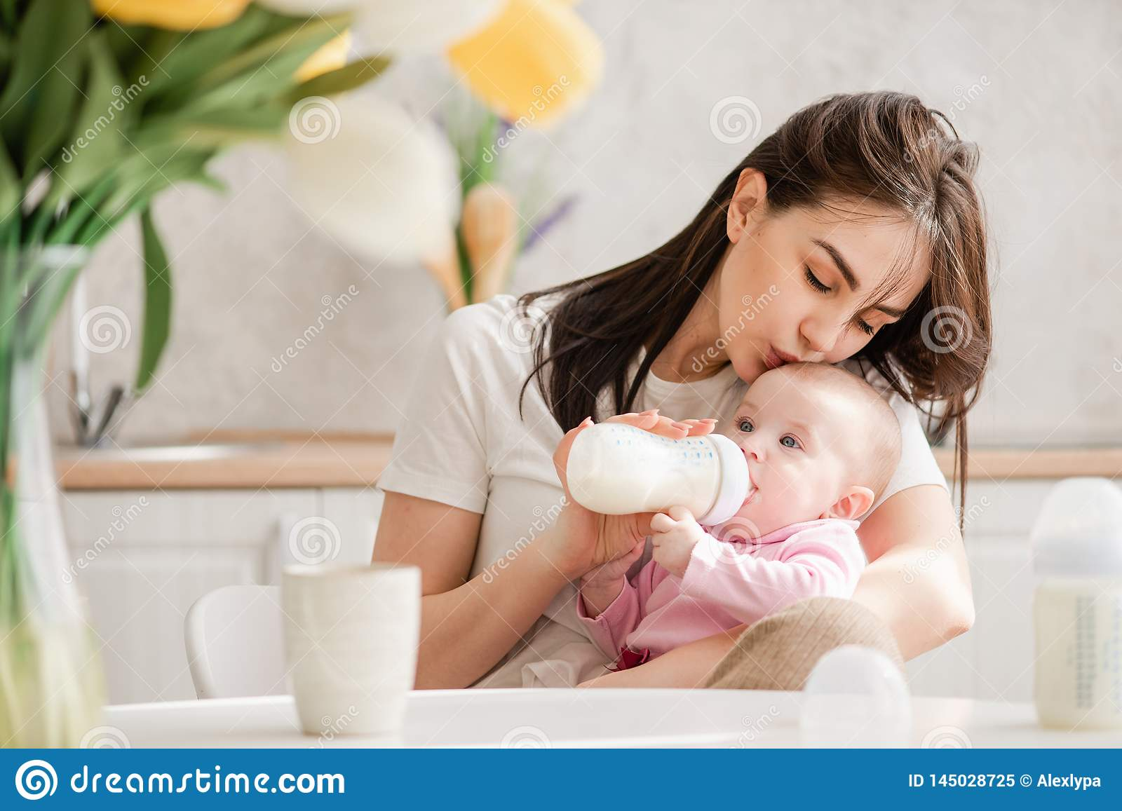 Young woman kiss baby during drinking milk