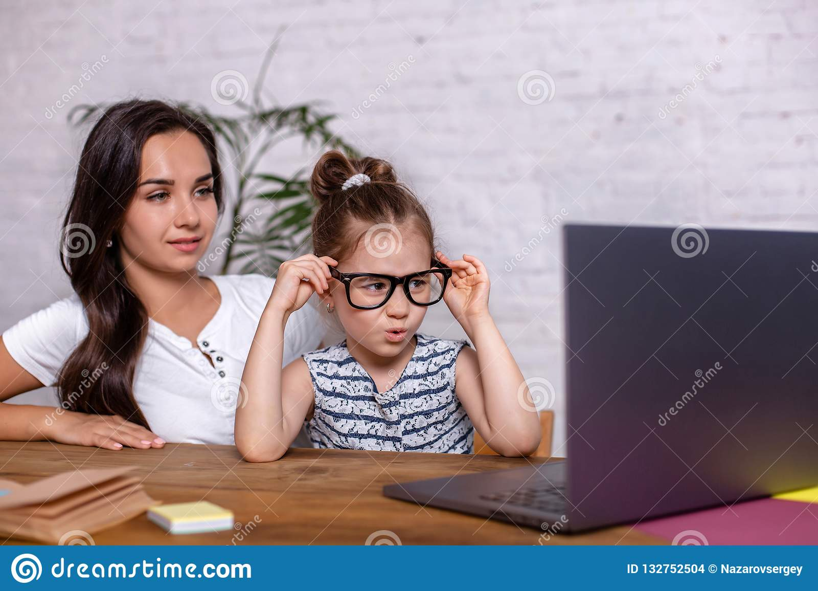 A young mother with little daughter are shopping on the Internet at personal computer