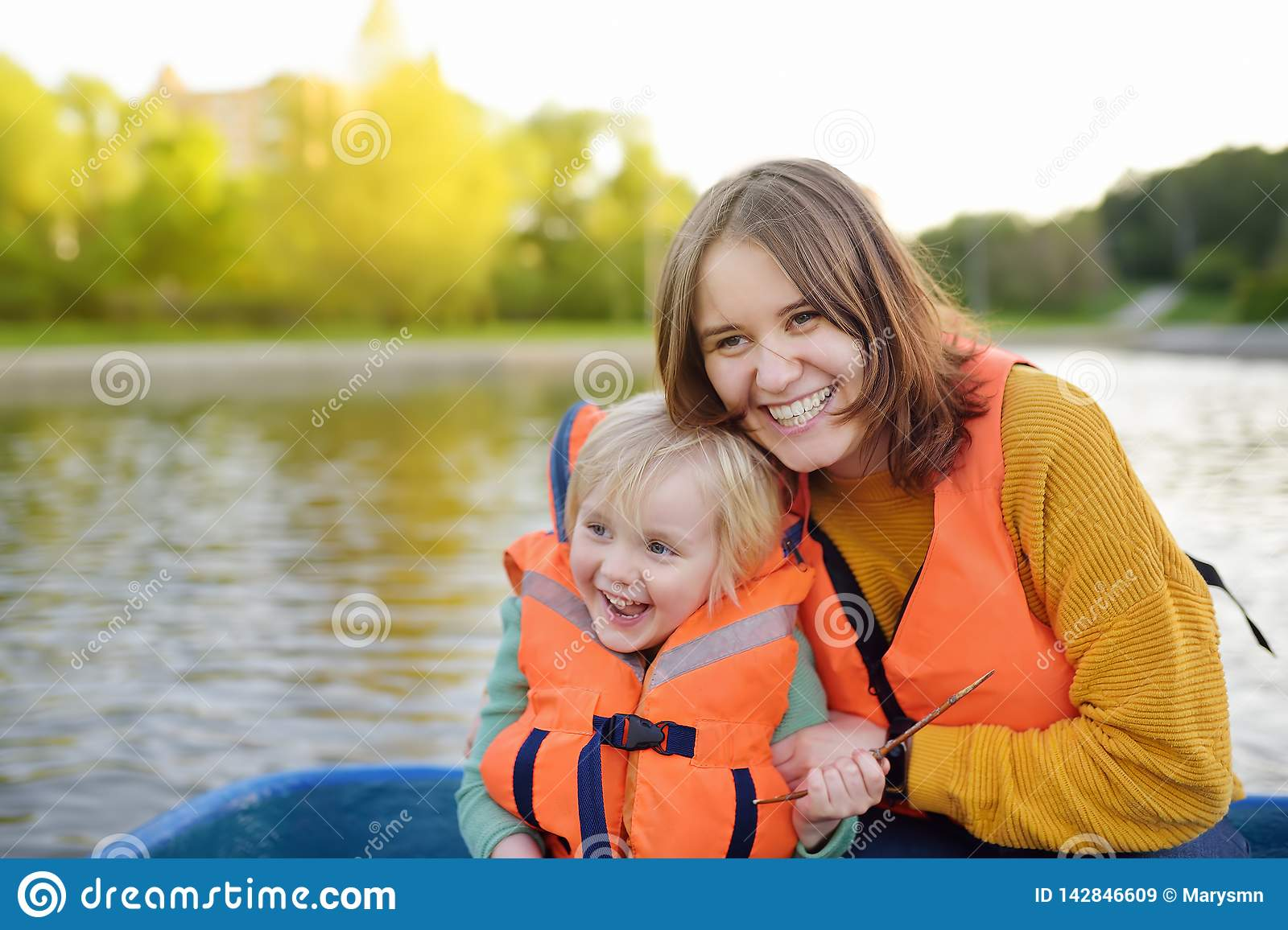 Young mother and little son boating on a river or pond at sunny summer day. Quality family time together on nature