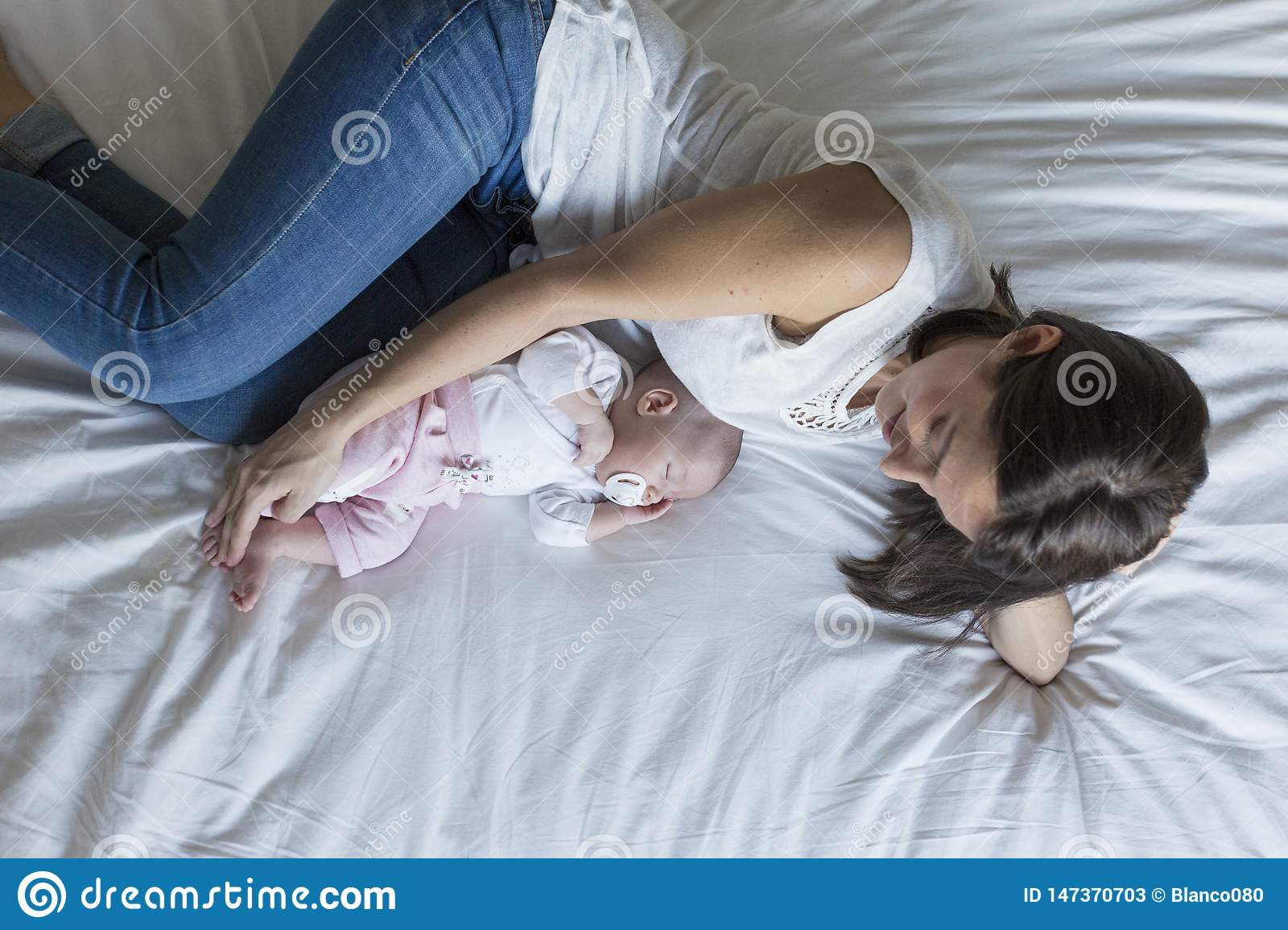 young mother lying on bed at home with her baby girl. family and love concept