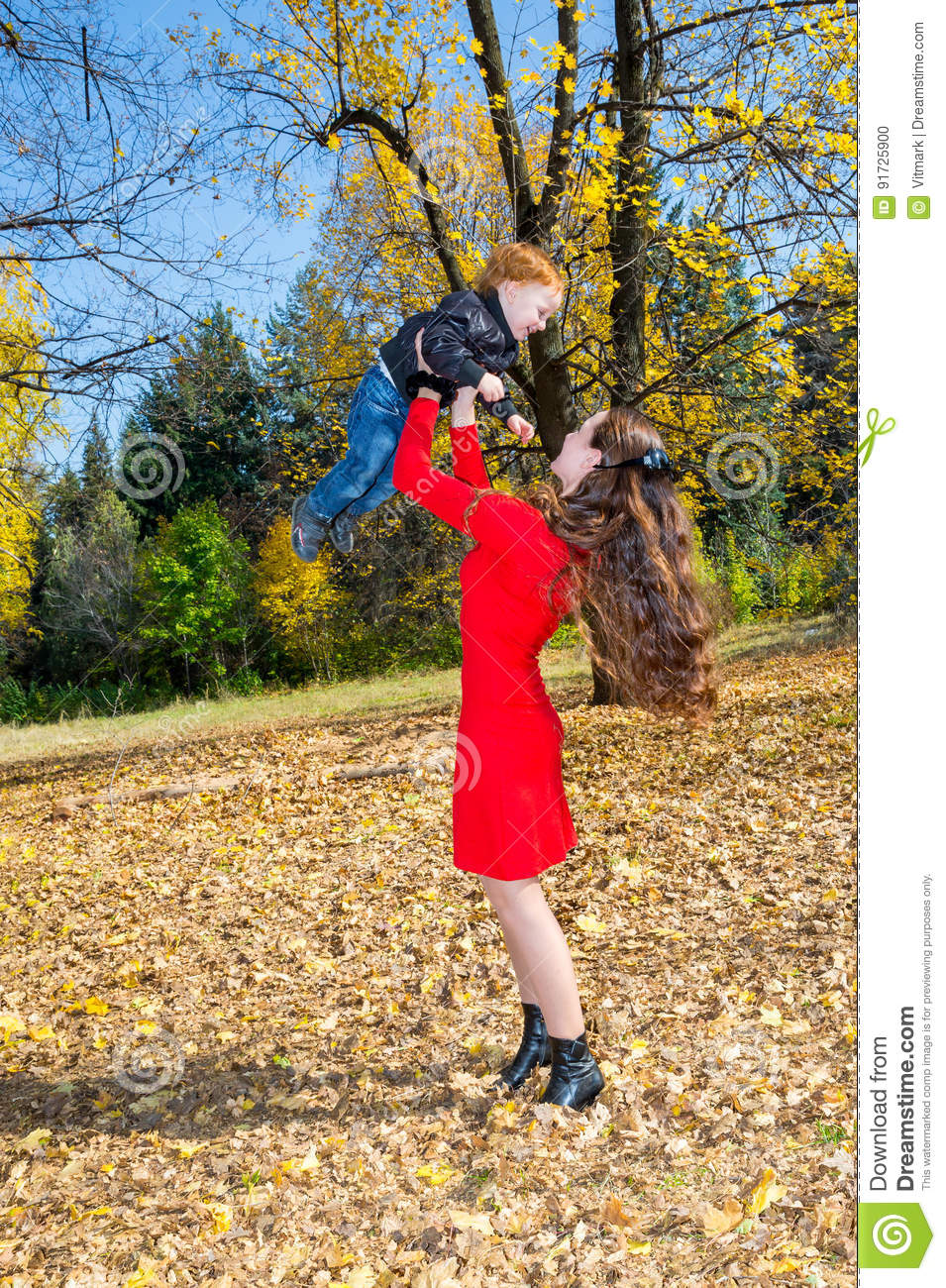 Young Mother and son in autumn park. happy family: mother and child boy play cuddling on autumn walk in nature outdoors