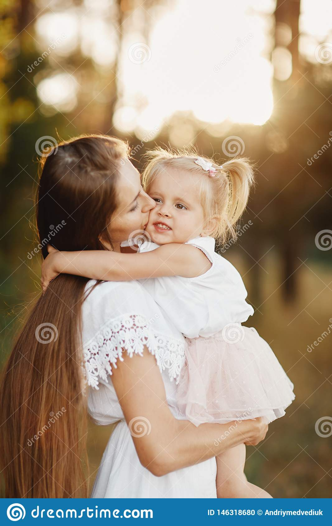Young mother taking care of her little baby girl. mom and her daughter outdoors. Loving family. Mother`s day concept