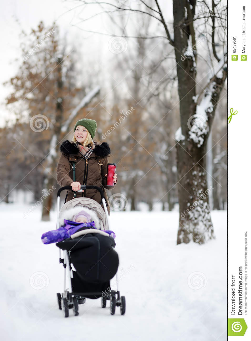 young mother walking with baby in stroller in winter park stock image