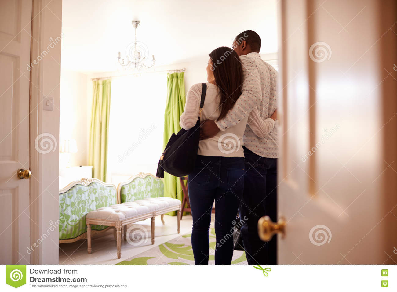Young multi ethnic couple looking at a hotel room, back view