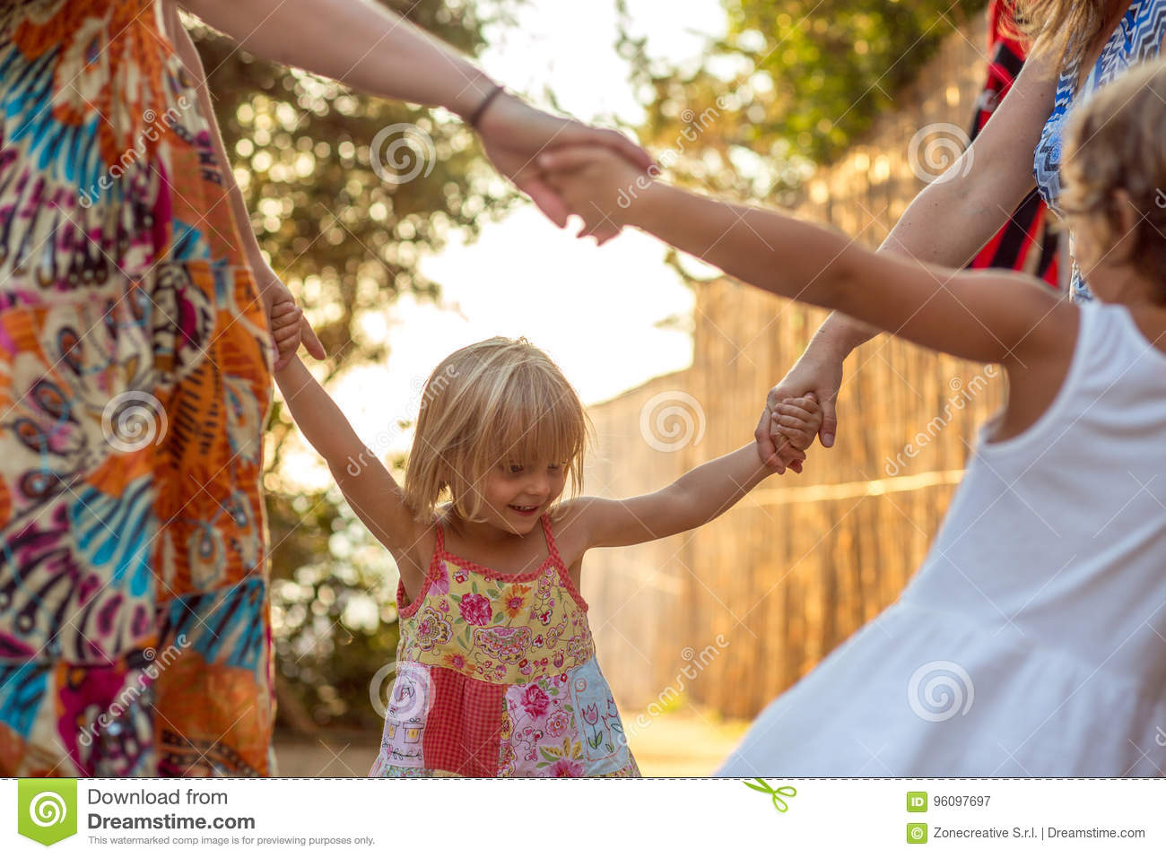 Young mum with blonde daughter girls smiling doing ring around the rosie . Warm sunset light. Family summer travel