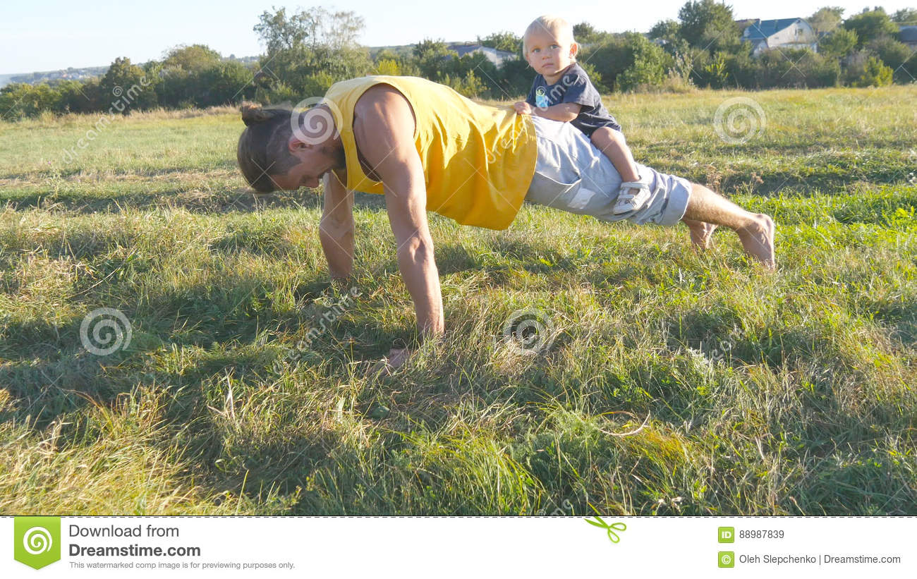 Young muscular father doing push ups with his little son on his back. Athletic man doing push-ups at green grass with